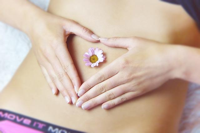 Frau, die mit ihren Händen um ihren Bauchnabel ein Herz formt. Im Nabel sitzt die Blüte eines Gänseblümchens