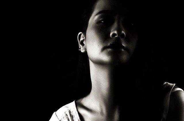 junges Mädchen, Teenager, halb im Licht, halb im Schatten, symbolisch im Übergang vom Mädchen zur Frau