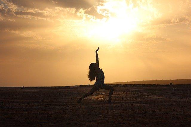 Frau, die vor dem Sonnenuntergang tanzt